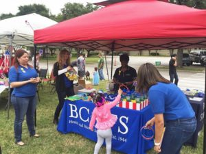 Photo: Girl playing a ring-toss game at BCFS table